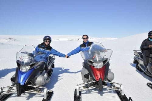 Snowmobile fun holding hands