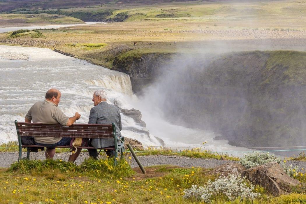 Men sitting at a bench in Iceland speaking Icelandic