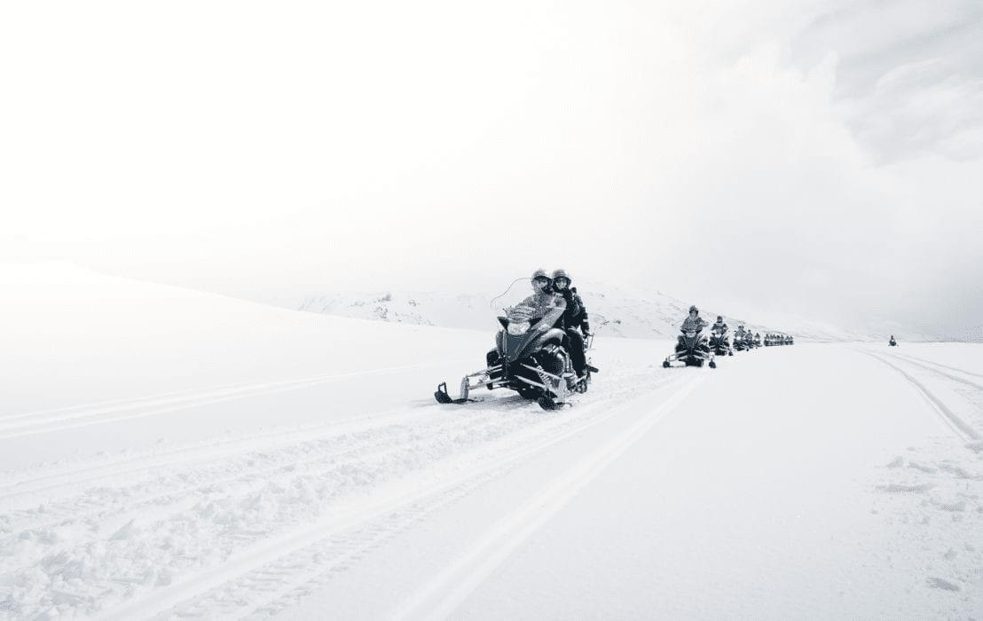 Snowmobiles dashing in whiteout